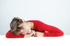 Young woman in a red sweater. A pensive young woman in a red sweater at the desk, isolated on white stock photos