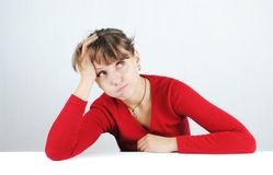 Young woman in a red sweater. A pensive young woman in a red sweater at the desk, isolated on white stock photo
