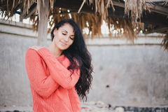 Young woman in a red sweater walking on the beach Royalty Free Stock Image