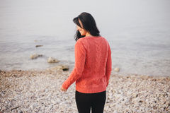 Young woman in a red sweater walking on the beach Royalty Free Stock Photography
