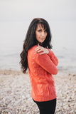 Young woman in a red sweater walking on the beach Stock Photography