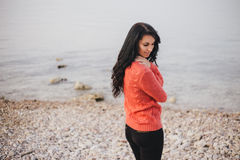 Young woman in a red sweater walking on the beach Royalty Free Stock Photos