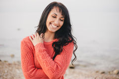Young woman in a red sweater walking on the beach Royalty Free Stock Photo