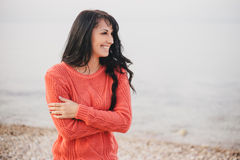 Young woman in a red sweater walking on the beach. Young woman with long curly hair in a red sweater walking on the beach stock images