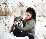 Young woman in red sweater in winter with husky wolf in snow for royalty free stock image