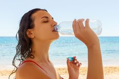 Young woman in a red swimsuit, drinking sparkling water from a transparent bottle on the beach Royalty Free Stock Photos