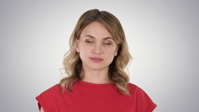 Young woman red t-shirt is walking, looking at camera on gradient background. Close up. Young woman red t-shirt is walking, looking at camera on gradient stock footage