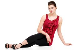 Young woman with red top and black pants sitting Stock Images
