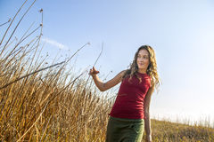 Young woman in red top walking on beautiful fall day in rural se. Young woman in red top walking on beautiful fall day in beautiful rural setting Royalty Free Stock Images