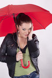 Young woman with red umbrella. Young shy woman under the red umbrella Royalty Free Stock Image