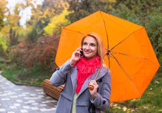 Young woman with red umbrella in beautiful autumn park Stock Images