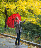 Young woman with red umbrella in beautiful autumn park Stock Photo