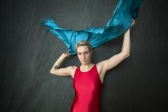Young woman in red unitard waving a blue scarf. Royalty Free Stock Photo