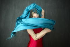 Young woman in red unitard waving a blue scarf. Royalty Free Stock Photography