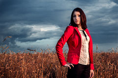 Young woman in red on a wheat field Stock Photos