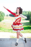 Young woman in red and white irish dance dress and wig posing Royalty Free Stock Photography