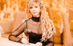 Young woman with red wine. Charming smiling young woman in black clothes with red wine glass sits at magnificent restaurant Stock Image