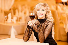 Young woman with red wine. Charming smiling young woman in black clothes with red wine glass sits at magnificent restaurant Stock Images