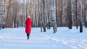 Young woman in red winter jacket and felt boots walks in pictorial city park with birches in frosty sunny winter day stock video footage