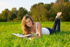 Young woman reeding on a green meadow Stock Image