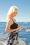 Young woman on reef at sea Stock Photography