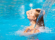 Young woman refresh in pool under the small waterfall Royalty Free Stock Photos