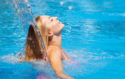 Young woman refresh in pool under the small waterfall Stock Image