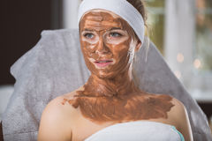 Young woman during refreshing chocolate mask treatment in spa Royalty Free Stock Photo