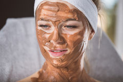 Young woman during refreshing chocolate mask treatment in spa. Smiling woman sitting in spa with chocolate mask applied on her face Royalty Free Stock Image