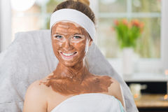 Young woman during refreshing chocolate mask treatment in spa. Smiling woman sitting in spa with chocolate mask applied on her face Royalty Free Stock Photo