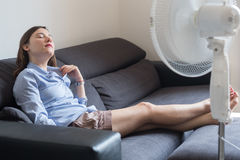 Young woman refreshing in front of cooling fan Royalty Free Stock Image