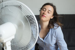 Young woman refreshing in front of cooling fan Stock Image