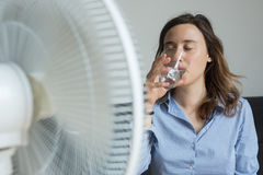 Young woman refreshing in front of cooling fan Stock Photography