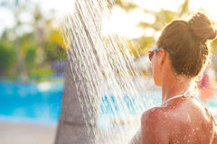 Young woman refreshing in shower near pool Stock Image