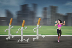Young woman refusing cigarettes. Portrait of a young woman running away by three cigarettes on the road with blur motion Stock Photography