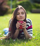 Young woman relax with cop of coffee in city park at summer day Stock Photography