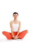 Young woman in a relax exercise sitting pose. Young woman sitting cross leg in a relaxing exercise pose staring at camera Royalty Free Stock Photos