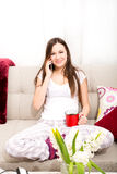 Young woman relax at home talking by phone Royalty Free Stock Photos