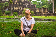 Young woman relax in lotus pose. Happy young woman relax in lotus pose on grass stock photos