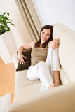 Young woman relax lying down on sofa Stock Photography