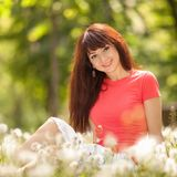 Young woman relax in the park with flowers. Beauty nature scene with colorful background, trees and flowers at summer season. stock photography