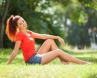 Young woman relax in the park on green grass. Beauty nature scene with colorful background, trees at summer season. stock image