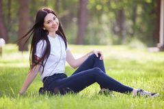 Young woman relax in the park on green grass royalty free stock photography