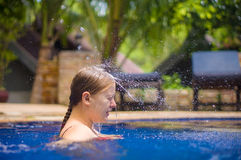 Young woman relax in pool under water shower stream fall to head Royalty Free Stock Images