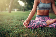 Young woman relax in yoga pose on the grass Royalty Free Stock Photo