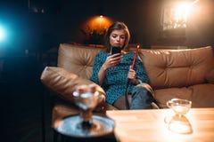 Young woman relaxation, smoking hookah at the bar Stock Photos