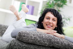 Young woman relaxed lying on couch at home Stock Photos