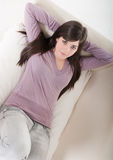 Young woman relaxed lying on couch home interior. Royalty Free Stock Image