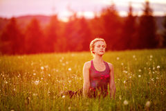 Young woman in a relaxed pose in the evening meadow Royalty Free Stock Photo