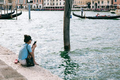 Young woman relaxes on the bank of Grand Canal browsing mobile phone. Stock Photography